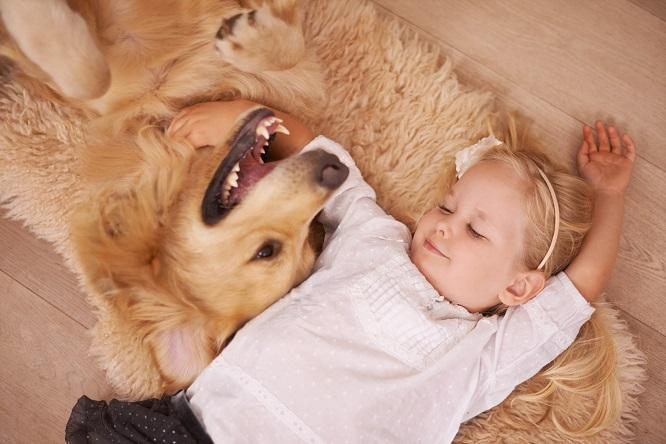 子どもと犬が幸せそうに寝転ぶ様子